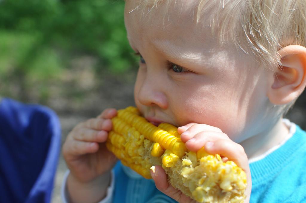 Kid eating corn